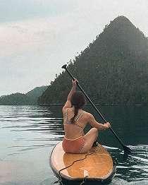 Membelakangi Kamera Dalam Balutan Bikini, Nikita Willy Santai Dayung Papan Selancar Saat Liburan di Pulau Wayag.